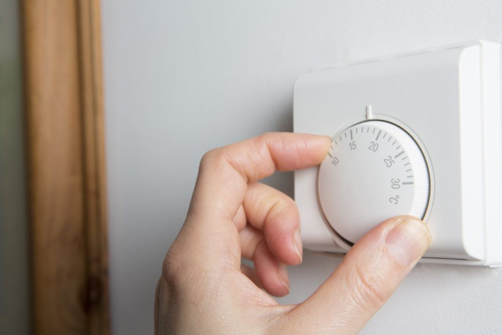 Close-Up-Of-Female-Hand-On-Central-Heating-Thermostat-Image