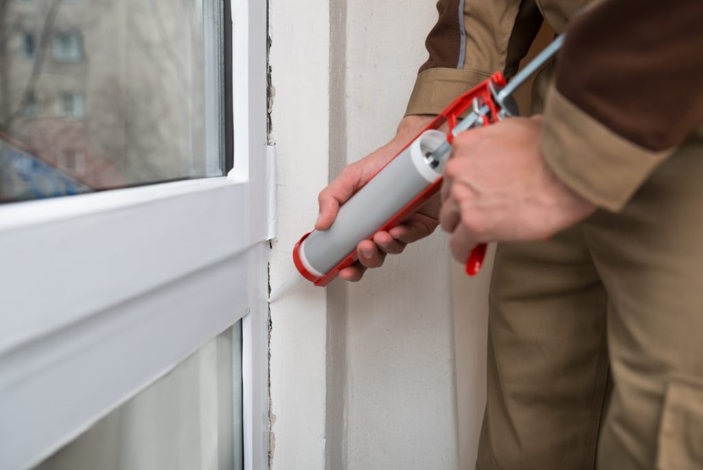 Close-up-Of-Person-Hands-Applying-Silicone-Sealant-With-Caulking-Gun-Image
