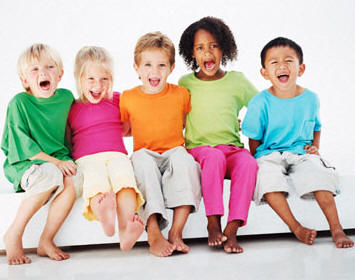 Five diverse children sitting and smiling
