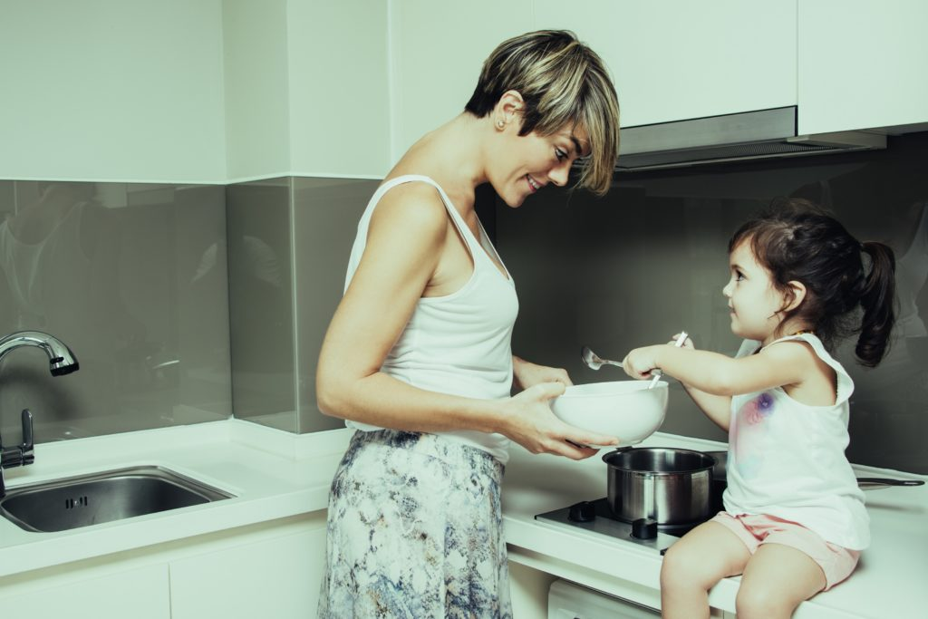 Little-daughter-helping-mom-at-kitchen-Image
