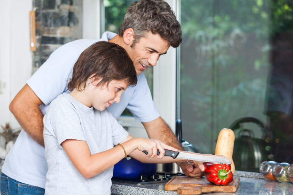father-and-son-smile-cooking-at-home-kitchen-slicing-vegetables-Image