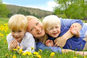 happy-young-mother-is-laying-outside-hugging-her-two-young-children-in-a-field-of-Dandelion-flowers-on-a-Spring-day