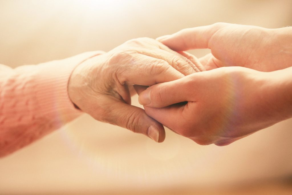 Old-and-young-holding-hands-on-light-background-closeup-Image