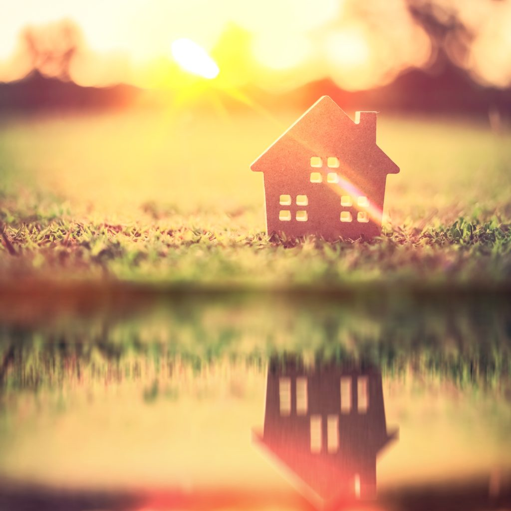 Copy-space-of-home-and-life-concept-Small-model-home-on-green-grass-with-sunlight-abstract-background-and-river-water-reflection-Image