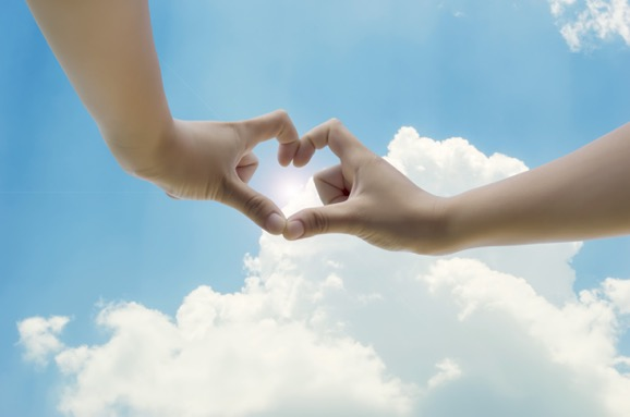 two-hands-making-a-heart-shape-with-the-sky-background