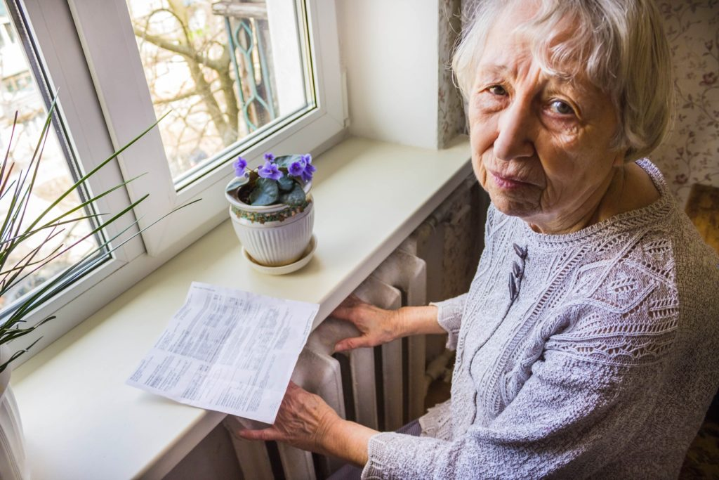 The-senior-woman-holding-gas-bill-in-front-of-heating-radiator-Payment-for-heating-in-winter-Image
